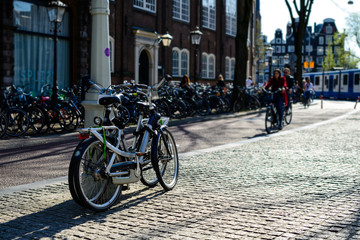 Bicycles parked on the city street on sunny day in Amsterdam, Th