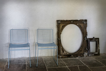 two chairs and a picture frame have been placed on the wall