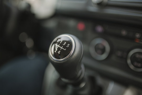 Close up of gear shift stick with 5 speed and reverse.