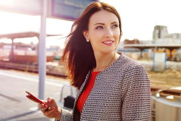 hübsche Frau mit Handy auf einem Bahnhof
