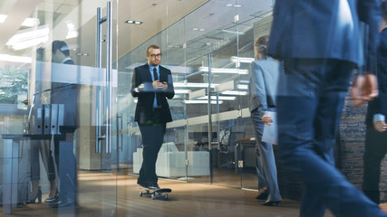 Stylish Suited Businessman Uses Smartphone Rides Skateboard Through the Corporate Building Hallway. Stylish Glass and Concrete Building with Multicultural Crowd of Business People.