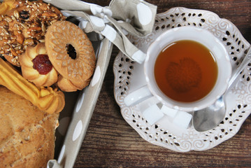 various cookies and biscuits baked at home in a container with polka dots and tea in a retro cup