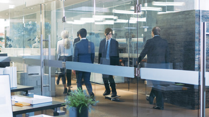 Suited Asian Businessman Rides Skateboard Through the Corporate Building Hallway. Stylish Glass and Concrete Building with Multicultural Crowd of Business People.