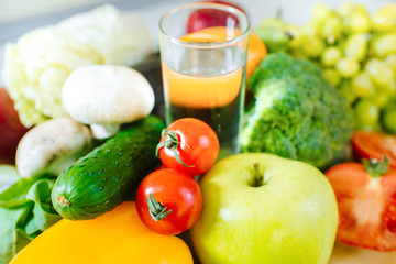 Many different fruits and vegetables with glass of water in the middle of