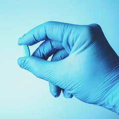 Unidentified doctor hand with latex glove holding a pill or caps