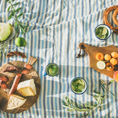 Photo sur Toile Pique-nique Flat-lay of summer picnic set with fruit, cheese, sausage, bagels and lemonade over striped blanket, top view, copy space, square crop