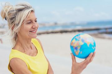lächelnde, ältere frau steht am strand und hält einen globus in der hand