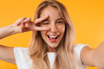 Cheerful young blonde girl showing peace gesture