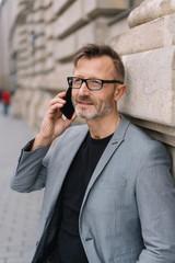 älterer mann steht in der stadt an einer hauswand und telefoniert