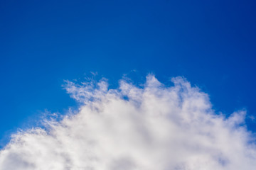 A curly summer clouds on blue sky background