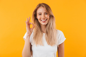 Portrait of a happy young blonde girl showing ok gesture