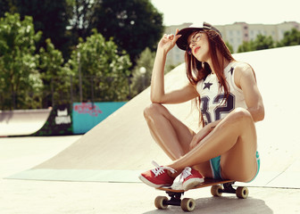 Beautiful young sexy girl sits on a skateboard in short green shorts, red sneakers, a baseball cap and sunglasses