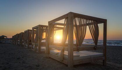 Silhouette wooden with blinds gazebo on an empty sandy beach on a sunset background.
