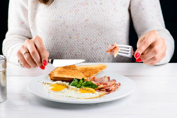 Process of eating tasty English breakfast with fried eggs, bacon