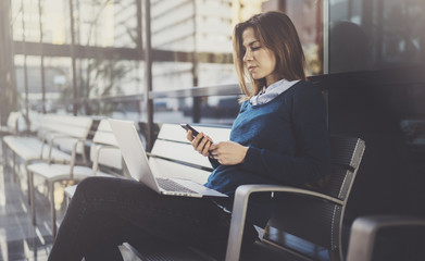 Attractive young businesswoman wearing casual clothes and working at business office center.Female using contemporary mobile laptop and smartphone while sitting in comfort bench.