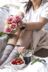 Romantic breakfast in bed. A bouquet of roses and a fragrant morning coffee. Fresh strawberries. Good morning, in the crumpled bed. Relax. Copy space