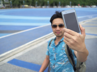 Young Asian tourist taking a photo or selfie. Selective focus and shallow depth of field.