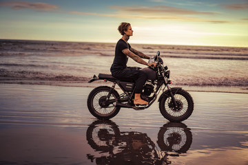 side view of tattooed man riding motorbike on ocean beach in summer