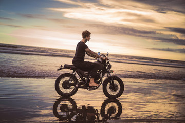 side view of tattooed man riding motorbike on ocean beach during beautiful sunrise