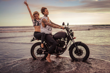 girlfriend showing peace sing during riding motorcycle on ocean beach