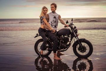 couple holding hands and sitting on motorcycle on ocean beach