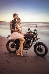 couple hugging on motorcycle on ocean beach during beautiful sunrise and looking at camera