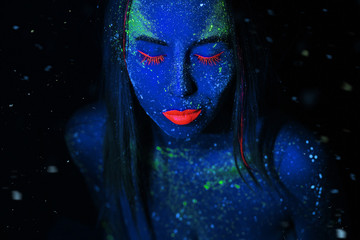 A girl with blue skin and cosmetic make-up, made of neon and fluorescent paints. The concept of star space in a person. Magic fantasy and dreams.