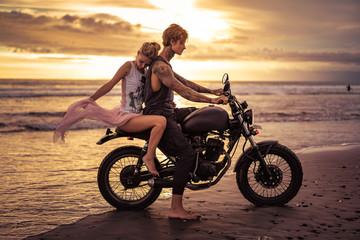 sensual boyfriend and girlfriend on motorbike on ocean beach during sunrise