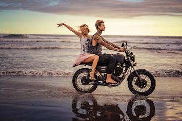 happy boyfriend and girlfriend riding motorbike on seashore during sunrise