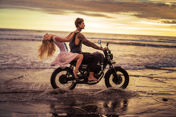 attractive couple riding motorcycle on ocean beach during sunrise