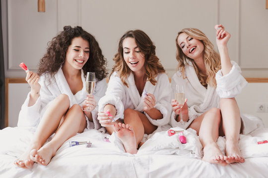 Portrait of gorgeous three women 20s wearing bathrobe sitting in big bed in posh apartment or hotel room, and painting nails during hen party