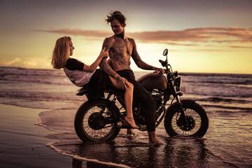 couple having fun on motorcycle at ocean beach