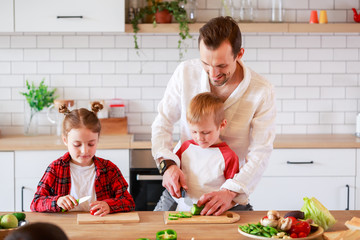 Photo of young father with daughter and son cooking at table