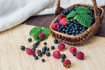 A basket with blueberries and raspberries on wooden background