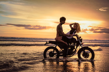 side view of passionate couple cuddling on motorbike at beach during sunset