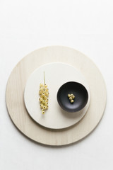 A composition of ceramics, white currants and wooden plates on a white surface.