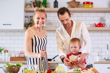 Photo of parents and young son preparing food in kitchen