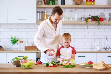 Photo of father and son cooking at table with vegetables