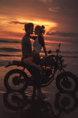 passionate couple hugging and going to kiss on motorcycle at beach during sunset
