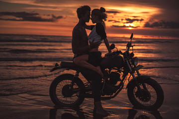 affectionate couple hugging and going to kiss on motorcycle at beach during sunset
