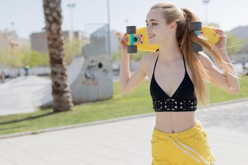 Blonde girl standing with penny board
