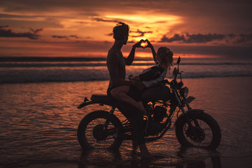 side view of couple making heart with fingers on motorcycle at beach during sunset