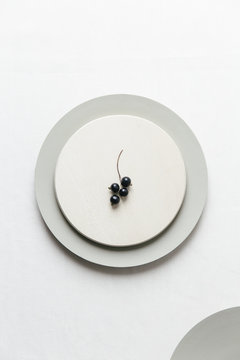Black currants on a plate on a white surface.