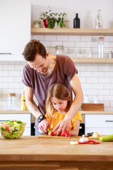 Photo of father with little daughter cooking salad