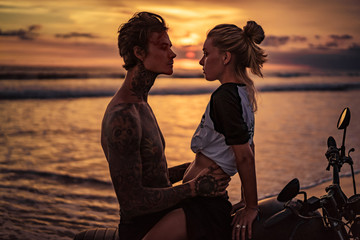 passionate couple hugging on motorcycle at beach during sunset