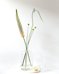 Floral arrangement in a glass vase with a glass set up for water & lemon drinks.