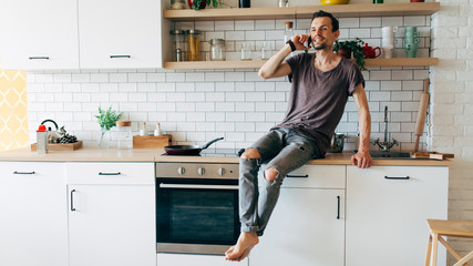 Photo of man sitting in kitchen talking on phone