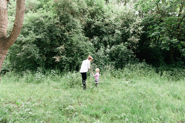 Woman and her young blonde daughter are picking wild flowers in the woods.