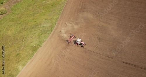 Wall mural Aerial panoramic video from the drone of agricultural fields, tractor with plow plows the land for sowing crops at spring evening in the summer. 4K.
