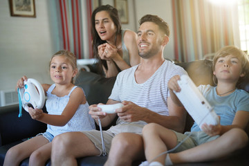 Family having fun at home playing video game